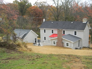 The back of the house, it all comes together with pop of color from the red tin roof over the laundry/mud room.