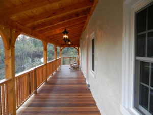 A great porch for rocking chairs with a view of the springhouse ruins. Mahogany floor boards and hemlock beams.